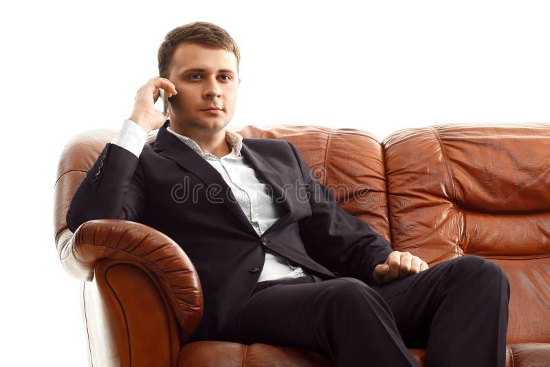 Téléphone parlant d'homme d'affaires se reposant sur le sofa photographie stock