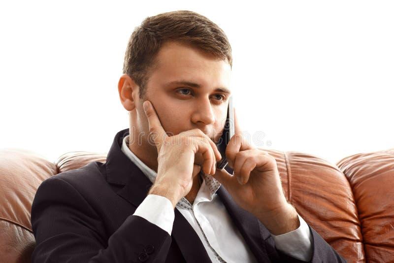 Téléphone parlant d'homme d'affaires se reposant sur le sofa photos stock