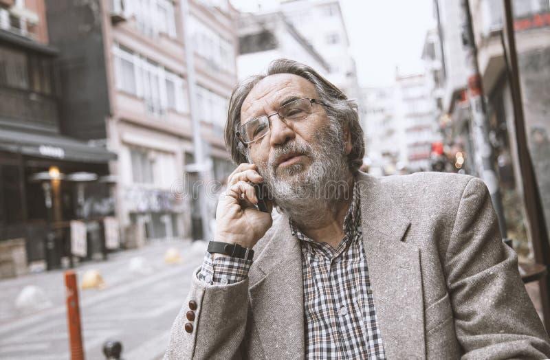 Téléphone parlant d'homme supérieur dedans dehors image libre de droits