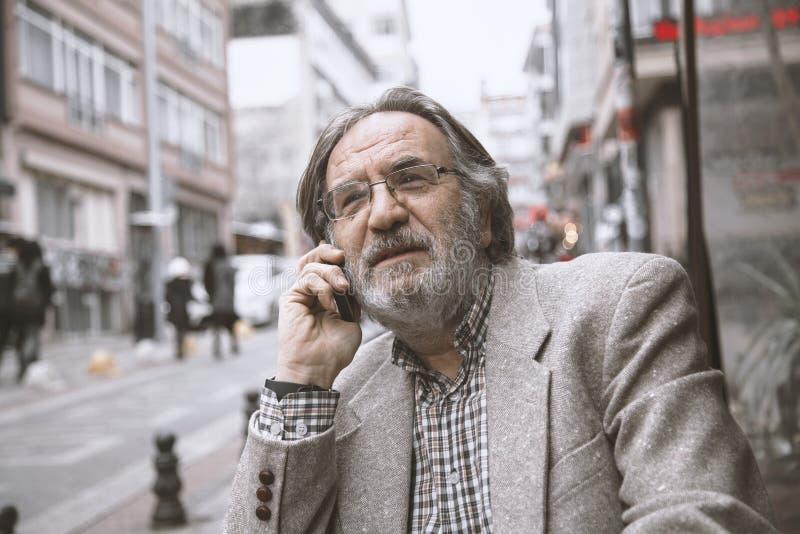 Téléphone parlant d'homme supérieur dedans dehors photographie stock libre de droits