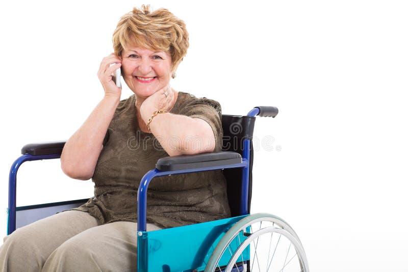 Téléphone parlant de femme supérieure handicapée images stock
