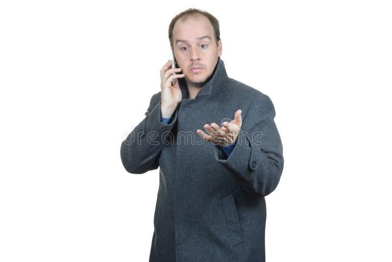 Téléphone parlant de manteau gris d'homme gesticulant image stock