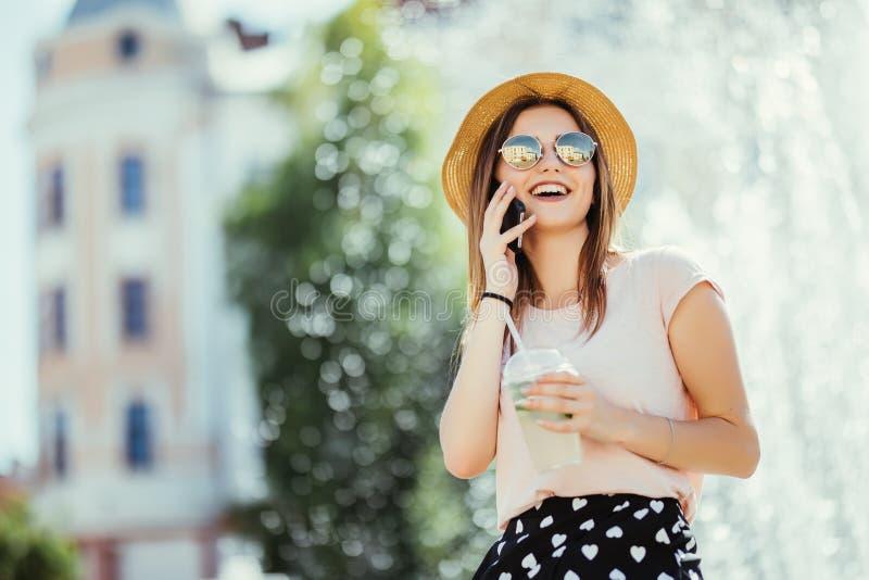 Téléphone parlant de sourire d'adolescente de jeune femme sur la lumière du soleil extérieure potable de mojito de rue d'été photo libre de droits