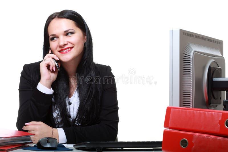 Téléphone parlant moderne de femme d'affaires se reposant au bureau image stock