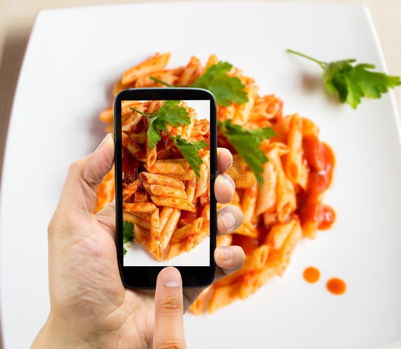 Téléphone photographiant avec des macaronis photo stock
