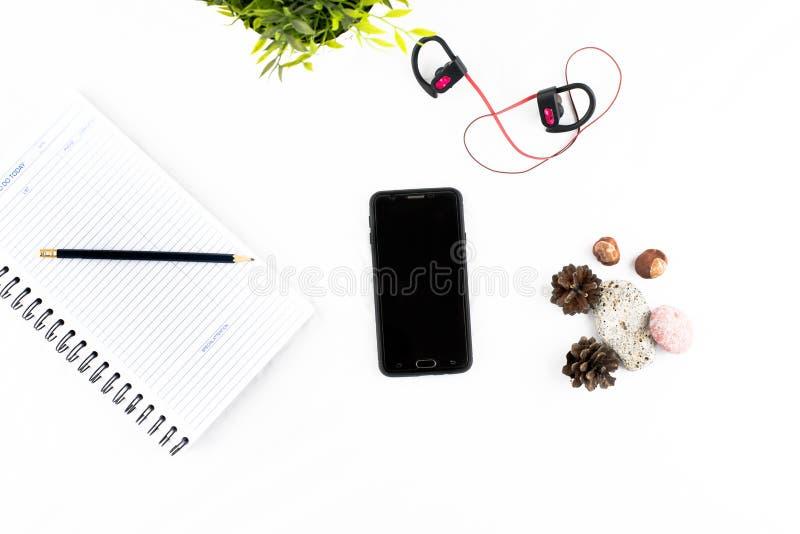 Téléphone portable, écouteurs, bloc-notes et crayon au-dessus de la table blanche photo stock
