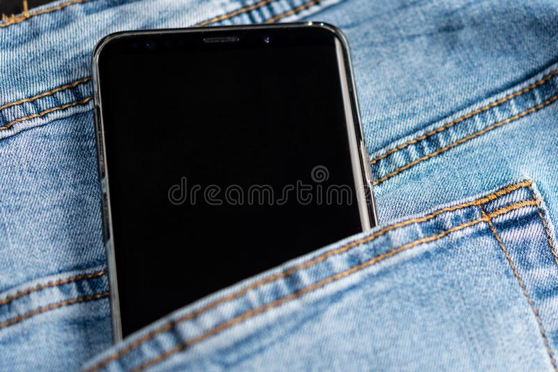 Téléphone portable avec l'écran noir pour l'espace de copie dans la poche de pantalon de jeans Concept de technologie des communi photos stock