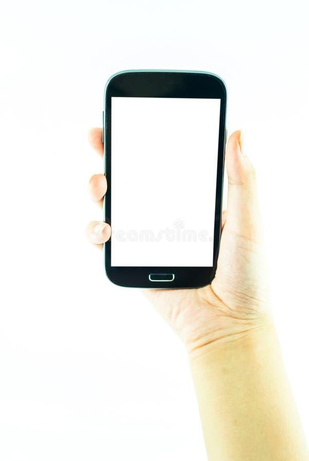 Téléphone portable avec l'écran tactile dans la main femelle sur le fond blanc image stock