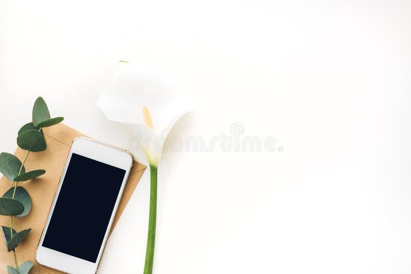 Téléphone portable avec l'écran vide et les fleurs sur le fond blanc, vue supérieure Voir les mes autres travaux dans le portfoli photographie stock libre de droits
