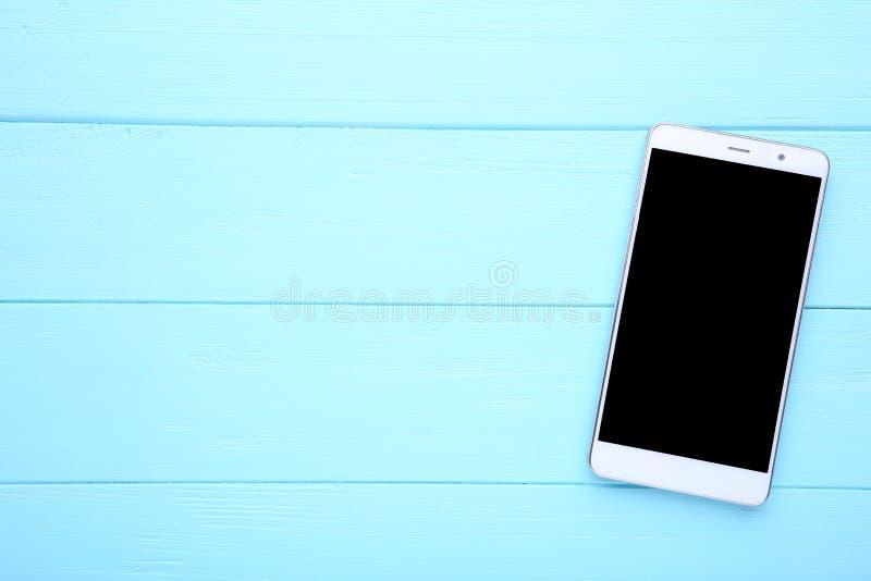 Téléphone portable avec l'écran vide sur le fond en bois bleu Smartphone sur le Tableau en bois photographie stock libre de droits