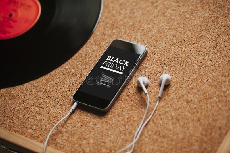 Téléphone portable avec la conception d'achats de Black Friday dans l'écran, les écouteurs blancs, et l'espace de copie image libre de droits