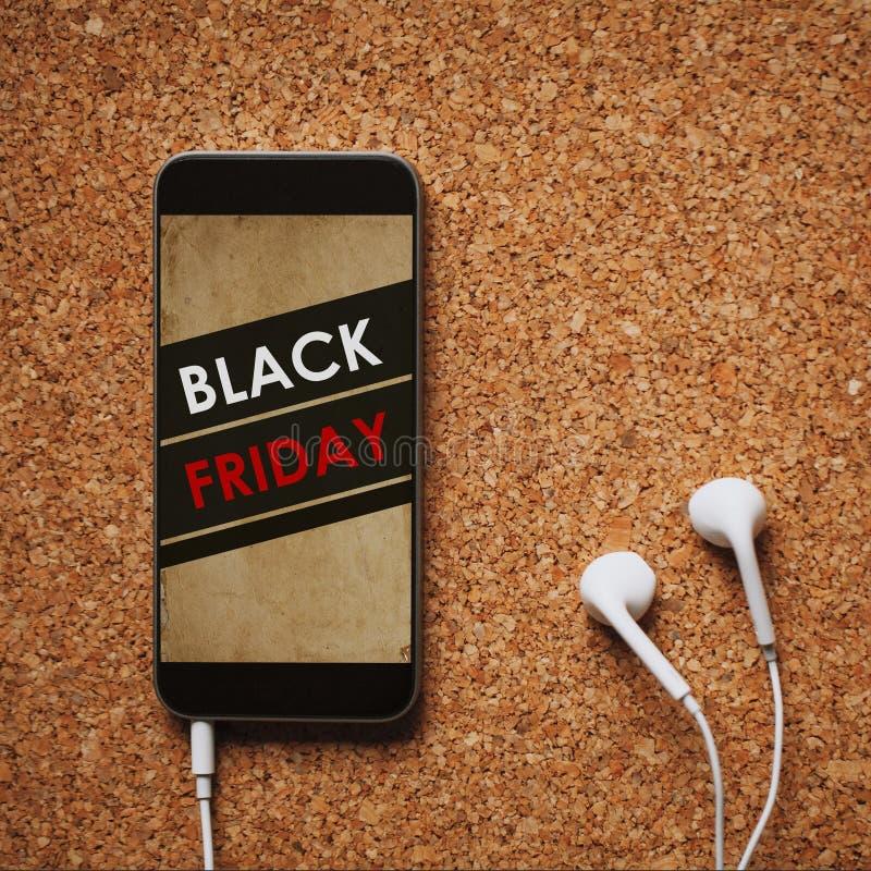 Téléphone portable avec le label de vente de Black Friday dans l'écran, les écouteurs blancs, et l'espace de copie photo libre de droits