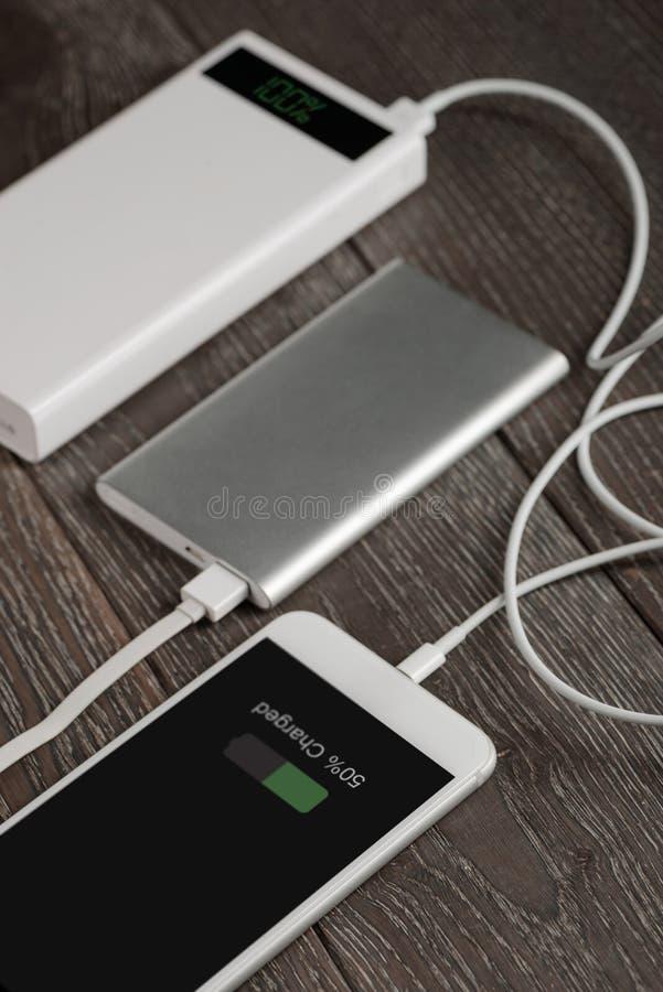 Téléphone portable chargeant par l'intermédiaire de la banque photo stock