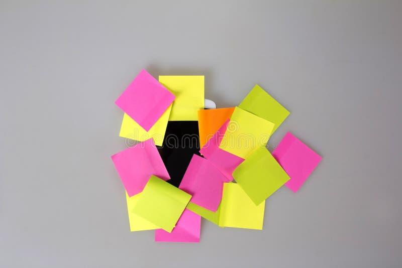 Téléphone portable couvert dans les notes de post-it vides colorées image libre de droits