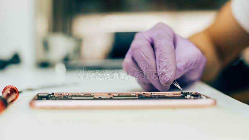 Téléphone portable défectueux de réparation de technicien dans le smartphone électronique t photos stock