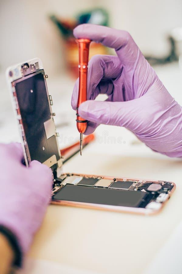 Téléphone portable défectueux de réparation de technicien dans le smartphone électronique t photo stock
