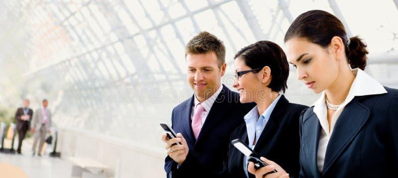 téléphone portable d'hommes d'affaires utilisant image stock