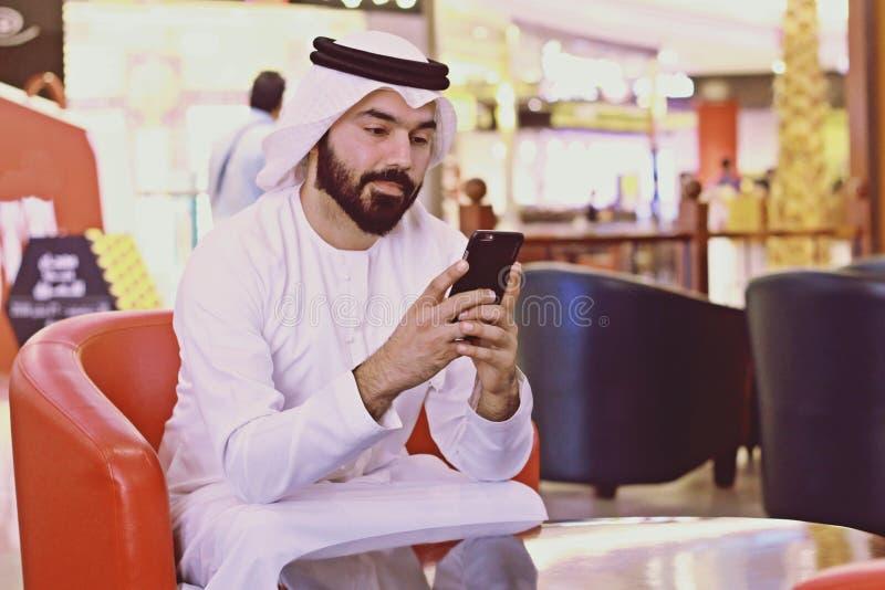 Téléphone portable d'Internet de Rich Arab Business Man Using dans la boutique de café photographie stock libre de droits