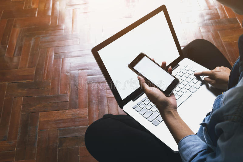 Téléphone portable d'utilisation de femme de l'Asie et ordinateur portable d'ordinateur photographie stock libre de droits