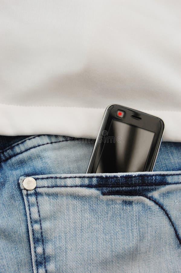 Téléphone portable dans des jeans photographie stock