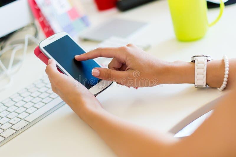 Téléphone portable dans la main d'une femme Image d'intérieur photographie stock