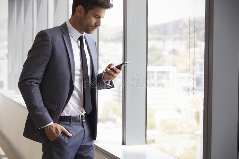 Téléphone portable de Checking Messages On d'homme d'affaires photos stock