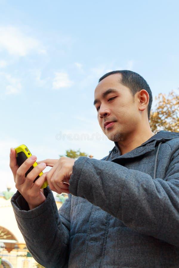 Téléphone portable de jeu d'homme image stock