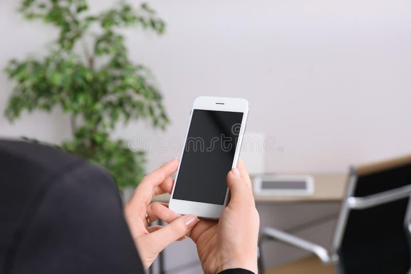 Téléphone portable de participation de femme avec l'écran vide dans le bureau, plan rapproché photo stock