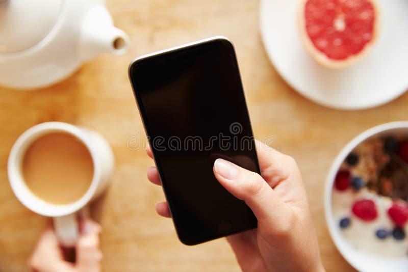 Téléphone portable de Person At Breakfast Looking At image libre de droits