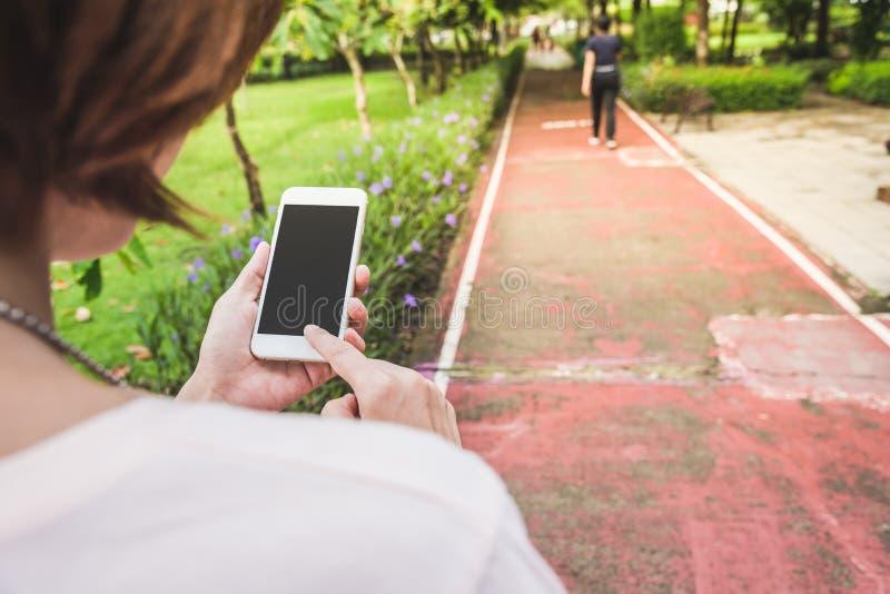 téléphone portable de prise de main dans le jardin photos stock