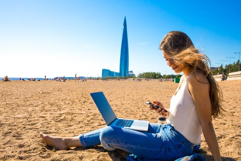 Téléphone portable de utilisation femelle après travail de distance sur le dispositif de carnet image libre de droits