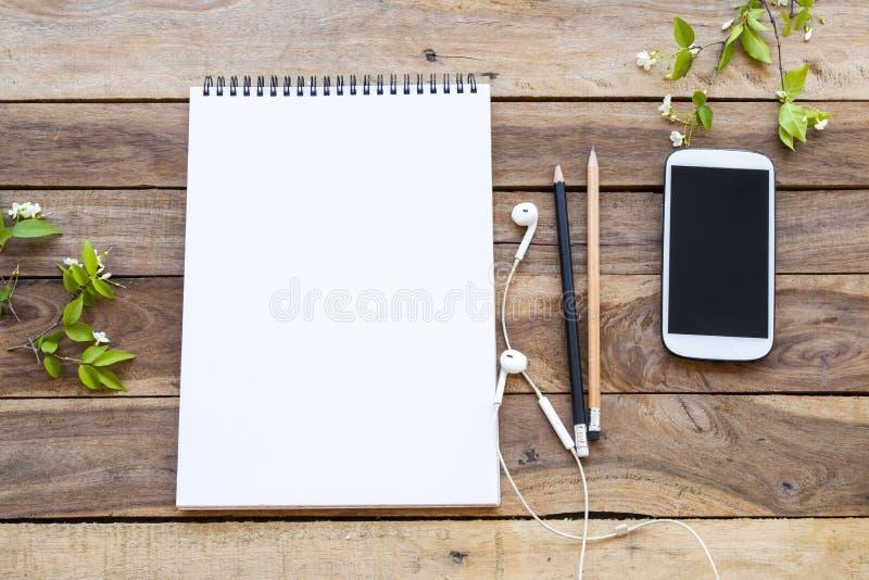 Téléphone portable et cahier de dessin pour l'organisation du travail à plat style sur fond de bois photographie stock