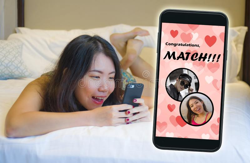 Téléphone portable et jeune belle et heureuse fille chinoise asiatique employant l'appli datant en ligne gai recevant un match av photo libre de droits