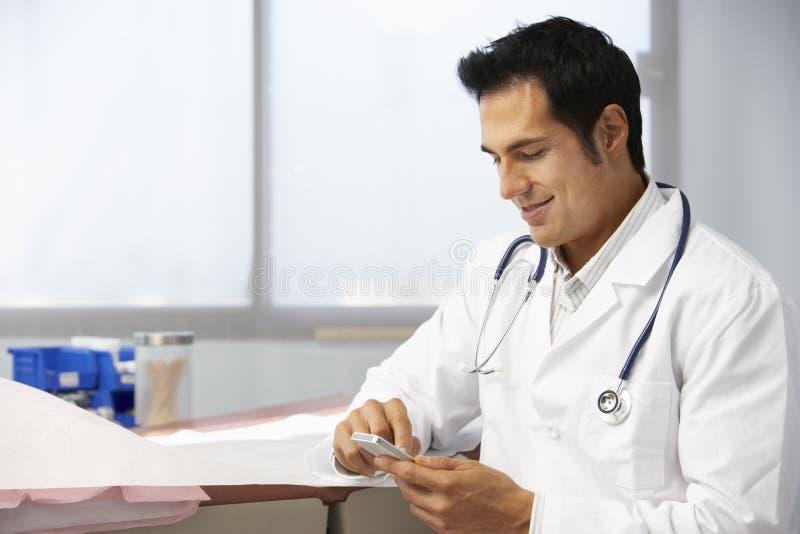 Téléphone portable masculin de docteur In Surgery Using photo libre de droits