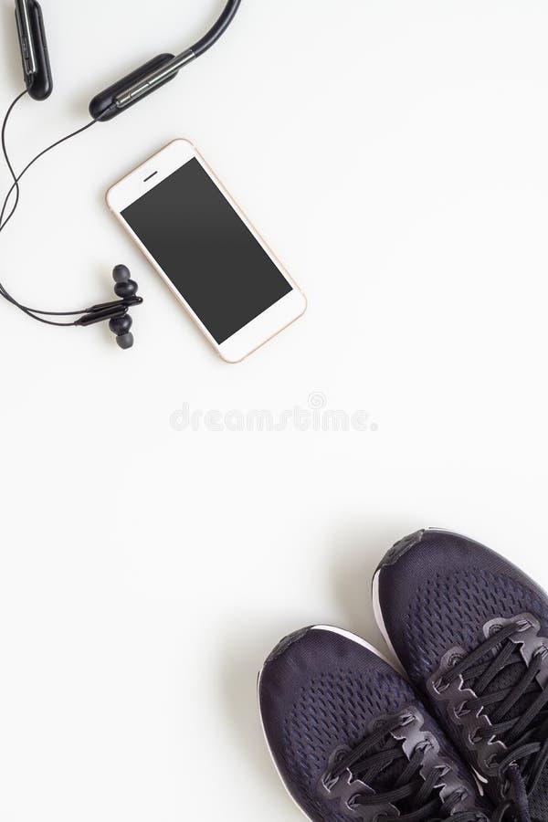 Téléphone portable mobile de maquette avec l'écouteur sans fil de bluetooth et les chaussures de course sur le fond blanc Modes d photographie stock libre de droits