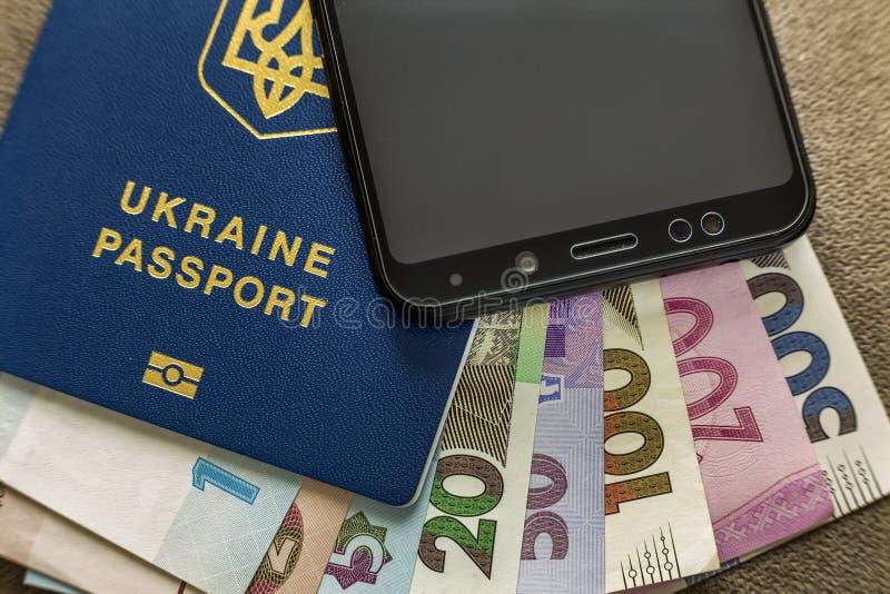 Téléphone portable noir moderne, factures de billets de banque de hryvnia d'argent et passeport ukrainien de voyage sur le fond d photo libre de droits