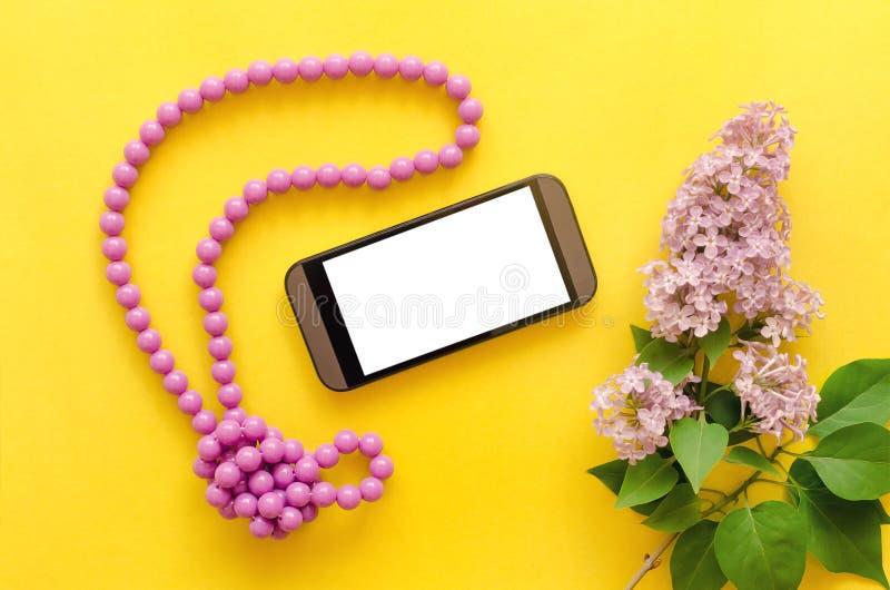 Téléphone portable, perles et fleurs lilas d'arbre photographie stock libre de droits