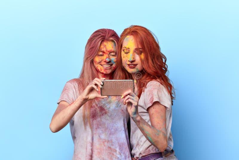 Téléphone portable positif heureux de participation de deux filles, le regardant photos stock
