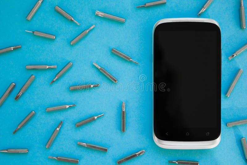Téléphone portable réparant, vue à plat étendue et supérieure, fond bleu, concept photographie stock