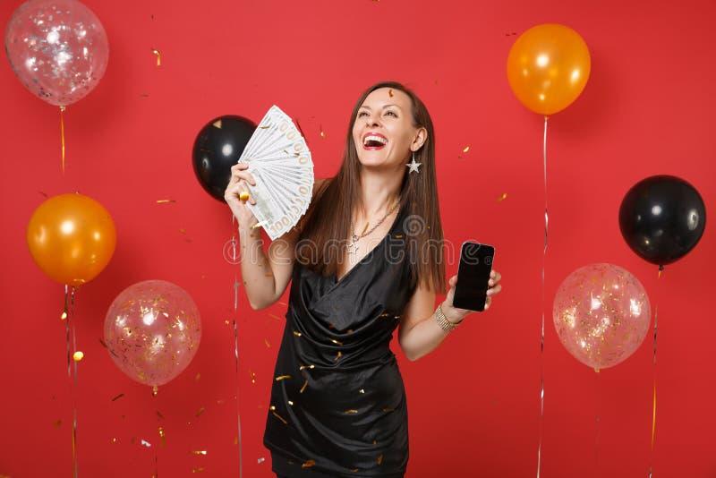 Téléphone portable riant de participation de jeune femme avec un bon nombre noirs vides vides de paquet d'écran de dollars, argen image libre de droits