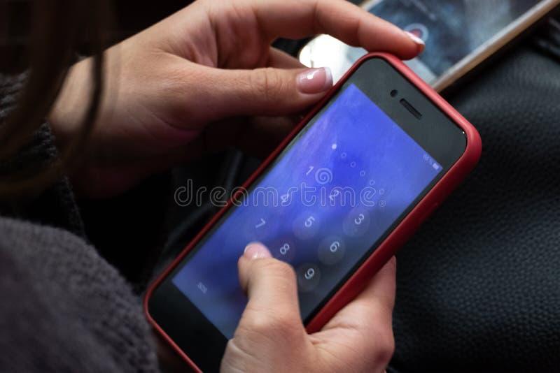 Téléphone portable rouge dans des mains femelles Une fille appelle ou les nombres de composition goupillent le code sur un smartp image stock