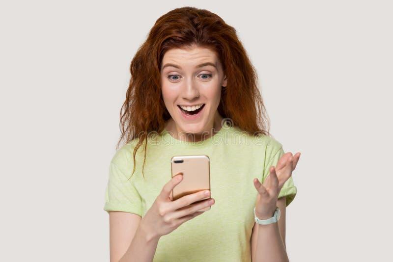 Téléphone portable roux étonné d'utilisation de fille choqué par des nouvelles inattendues photos stock
