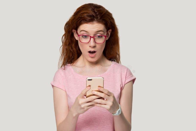 Téléphone portable roux étonné de prise de fille recevoir le message inattendu image stock