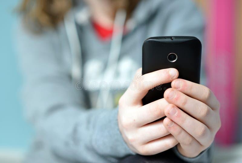 Téléphone portable se tenant de l'adolescence image libre de droits