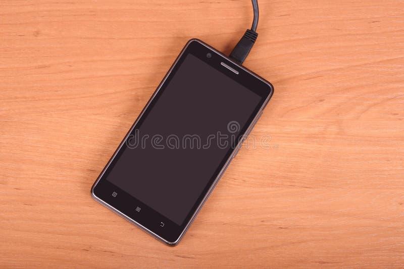 Téléphone portable sur le fond en bois photo libre de droits
