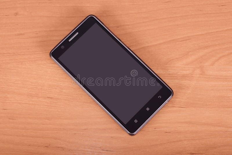 Téléphone portable sur le fond en bois photographie stock libre de droits