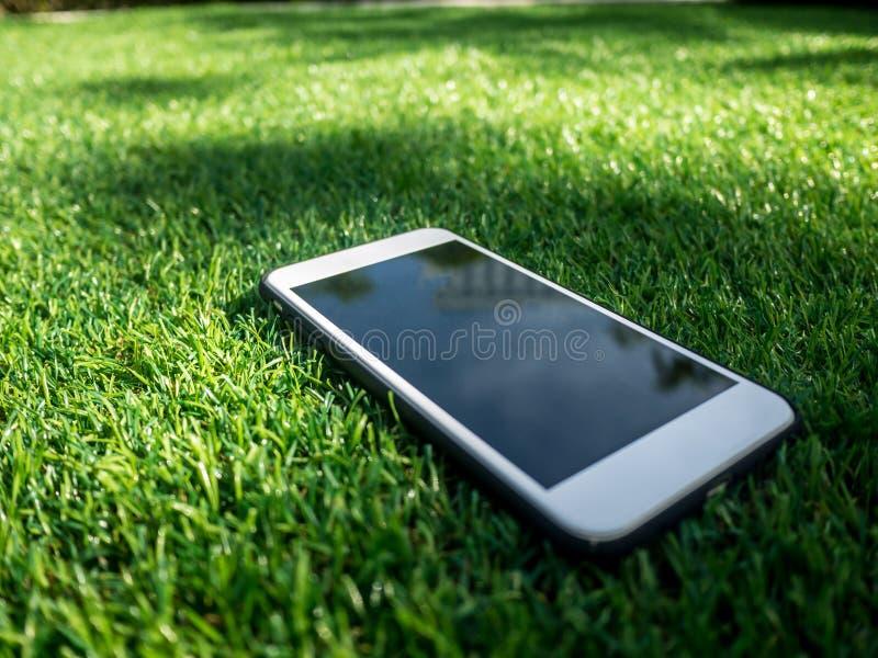 Téléphone portable sur un champ d'herbe artificiel photographie stock