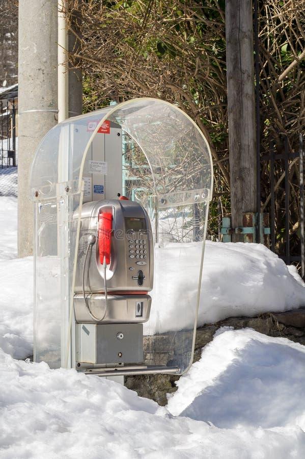 Téléphone public couvert par la neige image stock