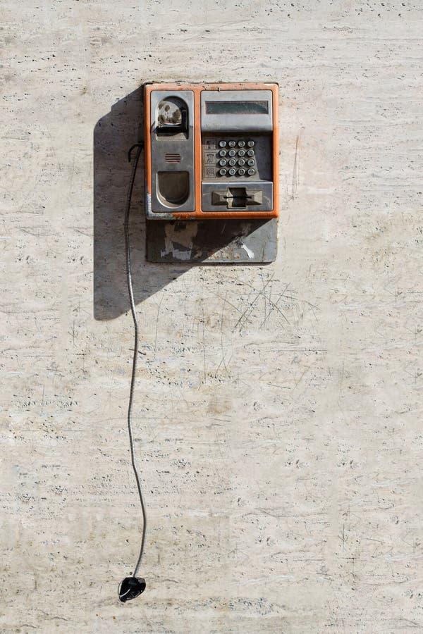 Téléphone public endommagé avec le combiné accrochant photos stock