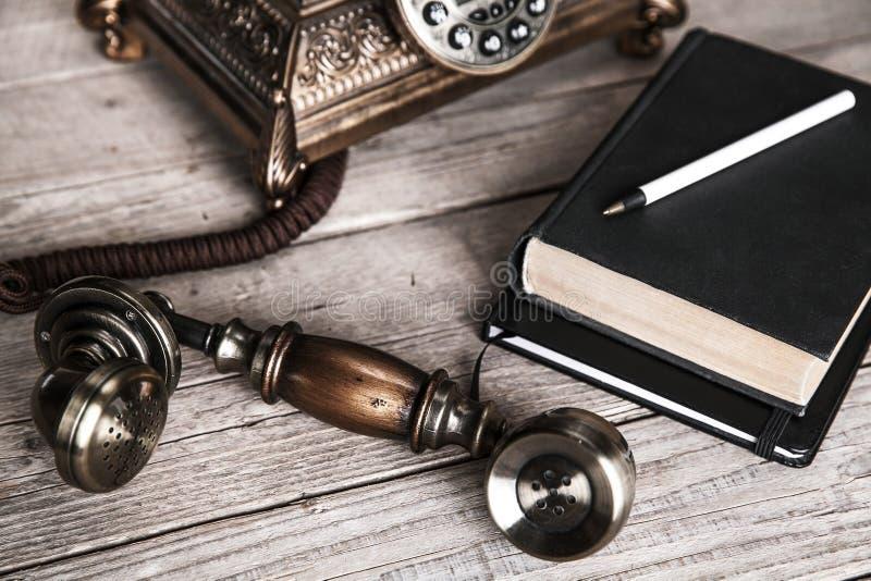 Téléphone rotatoire de vintage et vieil annuaire sur la table près du mur images libres de droits